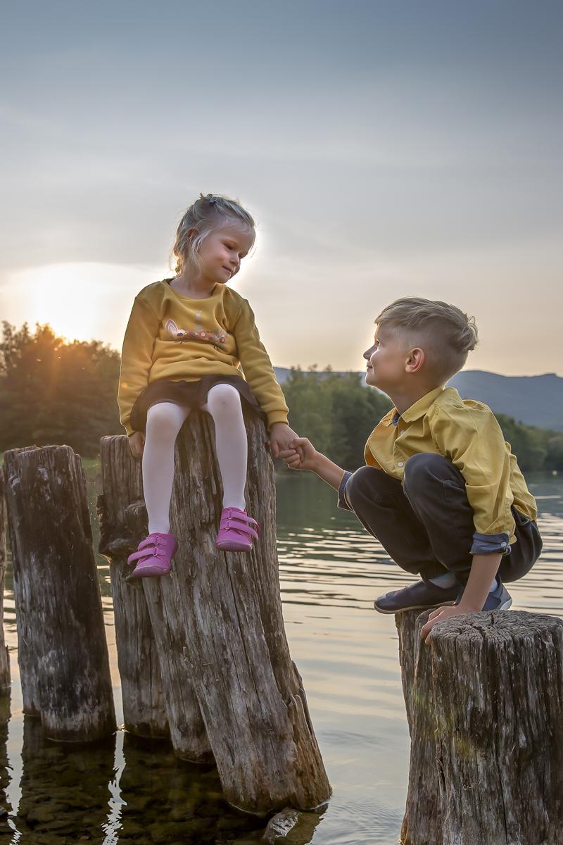 deti-sedi-na-drevenych-kulech-u-vody